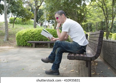 Men read a book on a bench in the park
