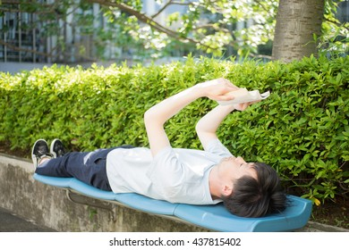 Men read a book while sleeping on a bench