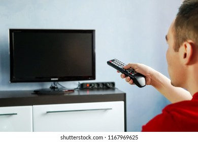 Men with the remote control, front of the television. Young guy switches channels on the remote from the TV. Turning the TV on or off