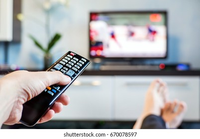 Men with the remote control front of the television. A man is relaxing on sofa and watching sports on TV.