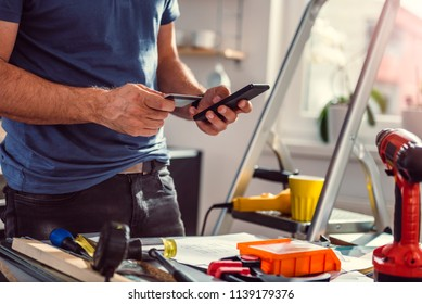 Men renovating kitchen and shopping construction material online on smart phone