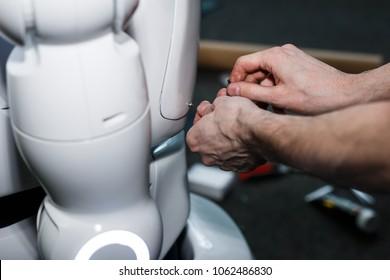 men repairs Modern white futuristic humanoid robot