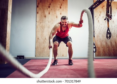 Men with rope in functional training fitness gym in a crossfit workout
