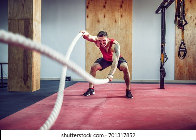 d6c8f5ac0b866 Men with rope in functional training fitness gym in a crossfit workout
