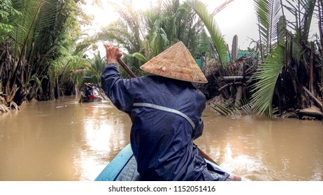 Men rowing in a Vietnamese hat rides a boat on the Mekong River in Vietnam. A serene river tour on the Mekong Delta, Can Tho Vietnam.
