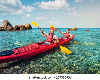 Men sailing kayaking on the clear water of the sea.