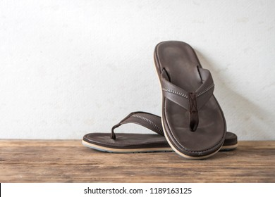 Men sandals footware brown on wood grunge table desk with copy space.