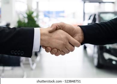 Men shake hands at car dealer showroom