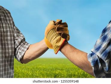 Men shaking hands in field
