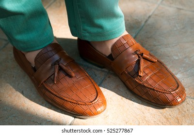 men shoes street city walk.Young man wearing beige chamois shoes with suite and short pants on stones background in a cloudy day.beautiful black boots perforation glyassazh shine style firmware design