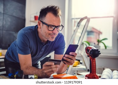 Men shopping construction material online during kitchen renovation on smart phone