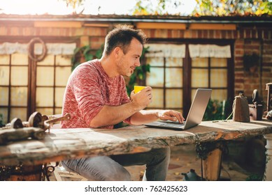 Men sitting in the at backyard patio drinking coffee and using laptop