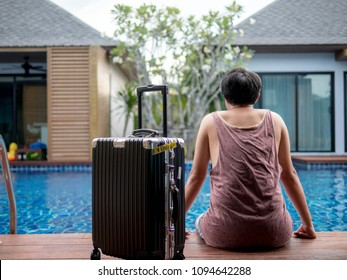 Men sitting by the pool with travel suitcase. Summer holiday traveling concept design banner with copyspace.