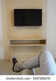 Men sitting cross-legged in front of TV