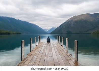 men sitting on a pier at Lake Nelson in New Zealand