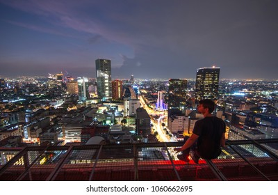 Men sitting on the rooftop Mexico city with night downtown view. Mexico City skyline at night from top
