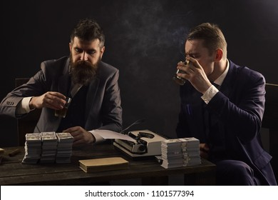 Men sitting at table with piles of money and typewriter. Businessmen discussing illegal deal while drinking and smoking, dark background. Illegal business concept. Company engaged in illegal business.