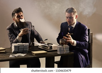 Men sitting at table with piles of money and typewriter. Company engaged in illegal business. Businessmen discussing illegal deal while drinking and smoking, grey background. Illegal business concept.