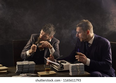Men sitting at table with piles of money and typewriter. Illegal business concept. Businessmen discussing illegal deal while drinking and smoking, dark background. Company engaged in illegal business