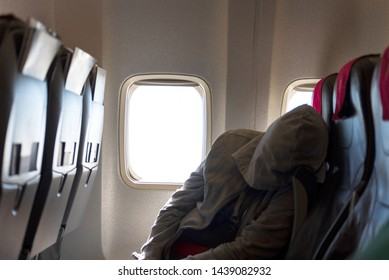 Men sleeping in an airplane during the flight. Bright window in the background