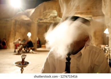 a Men smoking a Waterpipe in a cafe shop in the Village of Wadi Musa near the Temple city of Petra in Jordan in the middle east.  Jordan, Petra, April, 2009