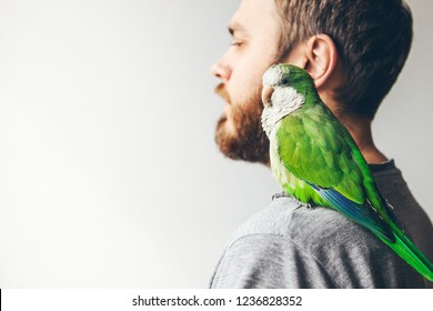 Men is spending time playing with his parrot. Happy Quaker Paraquat is sitting on shoulders and is looking at camera. Copy space area for your promo text or content.