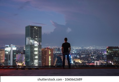Men standing on the rooftop Mexico city with night downtown view. Mexico City skyline at night from top