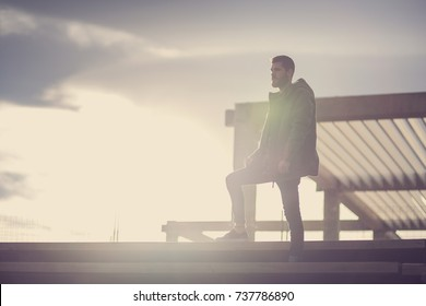 Men standing on the stairs at the sunset with the sky and clouds behind him.
