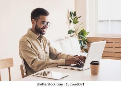 コンピューターで働く男子学生。自宅でノートパソコンを使用する実業家。インターネットマーケティング、フリーランスの仕事、オンライン教育のコンセプト