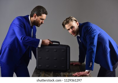 Men in suit or business partners with busy faces meet for deal. Business deal concept. Handover of briefcase with illegal goods. Businessmen with briefcase on dark background.