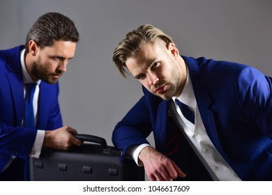 Men in suit or business partners with serious faces meet for deal. Business deal concept. Businessmen with black briefcase on dark background. Handover of briefcase with illegal goods or bribe.
