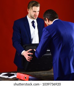 Men in suit or business partners with strict face meet for deal. Business exchange concept. Handover of briefcase with illegal goods. Businessmen with briefcase and folder on burgundy background.