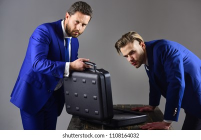 Men in suit or business partners with suspicious faces meet for deal. Businessmen with opened briefcase on dark background. Business exchange concept. Handover of briefcase with illegal goods.
