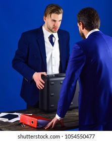 Men in suit or businessmen meet for handover of black briefcase and red folder. Business partners with strict face on blue background. Businessmen speaking about transaction. Business handover concept