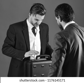Men in suit or businessmen meet for handover of black briefcase. Business partners with busy face on blue background. Businessmen speaking about transaction. Business handover concept.