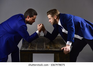 Men in suit or businessmen with tense faces compete in armwrestling on wooden table on dark background. Business competition concept. Businessmen fighting for leadership.
