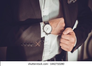 men suit perfect to the last detail.Man posing in black suit.closeup fashion image of luxury watch on wrist of man.body detail of a business man.Man's hand in a grey shirt with cufflinks.