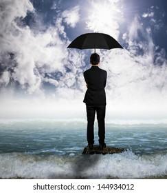Men in suit stand on rock holding black umbrella
