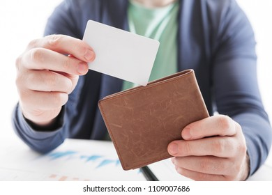 Men in suit with wallet and credit card. Selective focus of credit card in brown leather wallet. Business documents on office table  and  with social network diagram as Online shopping concept