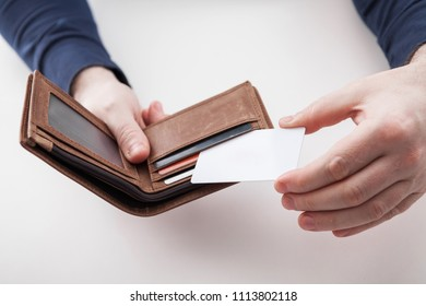 Men in suit with wallet and credit card. Selective focus of credit card in brown leather wallet.