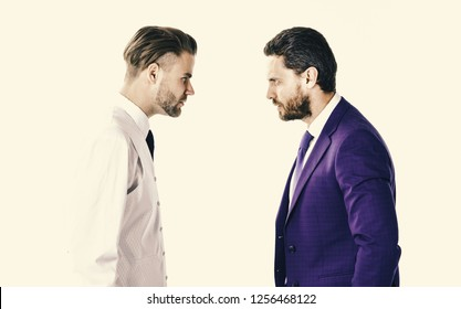 Men in suits or businessmen suspect each other of betrayal, isolated on white background. Businessmen and betrayal concept. Boss and employee or partners look at each other with tense expression.