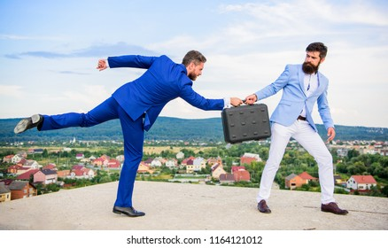 Men suits handover briefcase. Business deal landscape background. Businessman takes away briefcase from business partner. Fraud and extortion concept. Rascal racketeer extortionist cheating handover.