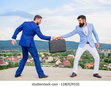 Men in suits handover briefcase. Business deal landscape background. Businessman takes away briefcase from business partner. Fraud and extortion concept. Man cheating while handover meeting.