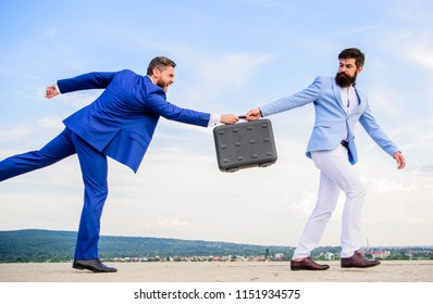 Men suits handover briefcase. Rascal racketeer extortionist cheating business transaction. Risky transaction. Fraud and extortion concept. Businessman takes away briefcase from business partner.