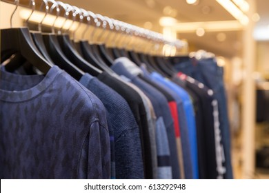 Men sweaters and shirts in different colors on hangers in a retail clothes store. Beautiful clothes for winter autumn season. Fashion industry for men.