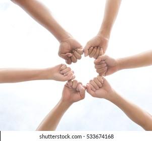 Men team put all hands together under white sky, selective focus