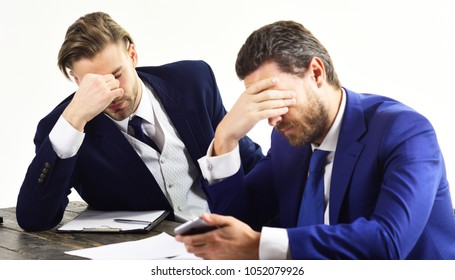 Men in with tired, worried faces read about business fail. Partners in formal suits look at smartphone. Bad luck, lack of money, company failure. Domino effect and failed business concept.