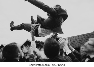 men tossing up groom at stylish wedding reception. groomsmen having fun and throwing up in air. emotional funny moment, space for text. joyful friends. black white photo