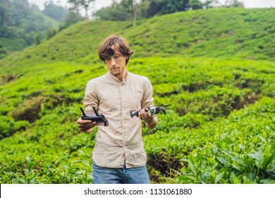 Men tourist tries to launch the drone at a tea plantation. Natural selected, Fresh tea leaves in tea farm in Cameron Highlands, Malaysia. Ecotourism concept.