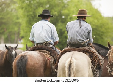 Men with traditional clothes on horseback in fields of Buenos Aires